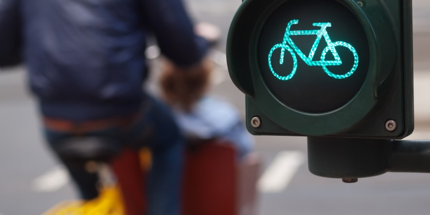 Traffic light bike sign in Germany with man riding his bike on the background